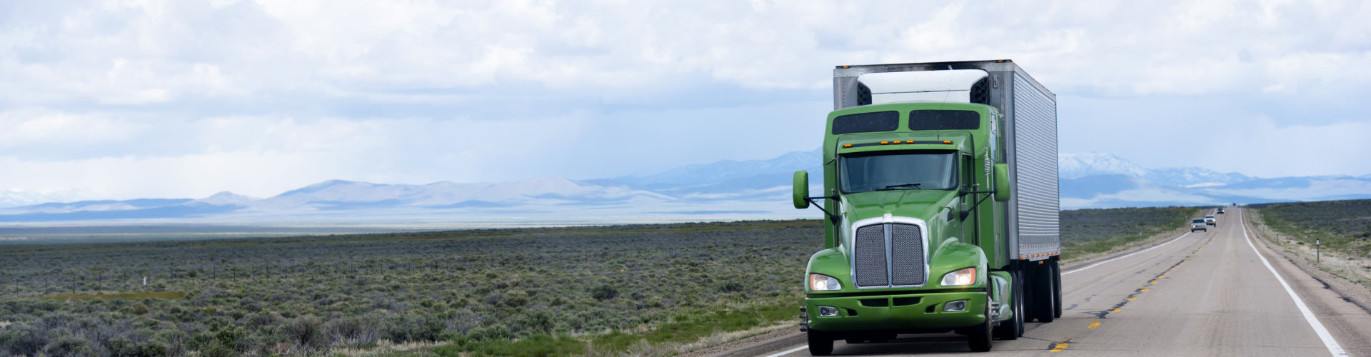 Stylish professional powerful green big rig semi truck with a trailer and refrigeration unit transporting perishable foods loads on a flat as an arrow road in hot Nevada desert. Photo Taken On: April 29th, 2016